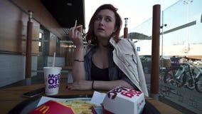 РИГА, ЛАТВИЯ - 22-ОЕ АПРЕЛЯ 2019: Молодая женщина есть в ресторане Mcdonalds фаст-фуда - большом Mac, среднем картофеле фри и кок акции видеоматериалы