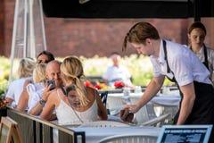 РИГА, ЛАТВИЯ - 31-ОЕ ИЮЛЯ 2018: Внешнее café на таблице сидит женщина с большой татуировкой на его назад за человеком пар рестор стоковая фотография rf