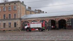 РИГА, ЛАТВИЯ - 16-ОЕ МАРТА 2019: Пожарная машина очищенный - водитель моет тележку пожарного на depo - сценарный взгляд акции видеоматериалы