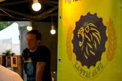 Рига, Латвия - 24-ое мая 2019: Бармен заказа пива Lauvas ждать следующего стоковые фотографии rf