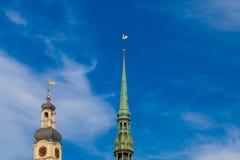 РИГА, ЛАТВИЯ - 6-ОЕ МАЯ 2017: Взгляд на церков ` s ` s StPeter Риги башни или куполка и башне купола Риги с стоковая фотография rf