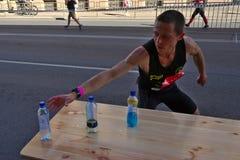 Рига, Латвия - 19-ое мая 2019: Кавказский бегун Томми элиты ища спорт выпивает стоковая фотография rf