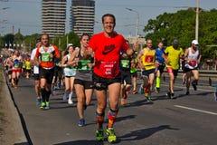 Рига, Латвия - 19-ое мая 2019: Средний достигший возраста человек счастливо продолжая марафон с обоими большими пальцами руки вве стоковые фотографии rf
