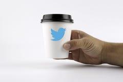 РИГА, ЛАТВИЯ - 19-ое октября 2015: Бумажный стаканчик кофе в руке и twitter подписывают Стоковая Фотография RF