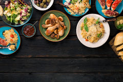 Ризотто, зажаренные в духовке ноги цыпленк цыпленка и закуски на темном деревянном столе Стоковая Фотография RF