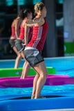 Римини, Италия - июнь 2017: Девушки делая тренировки на плавая циновке фитнеса в открытом бассейне Стоковые Изображения RF