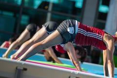 Римини, Италия - июнь 2017: Девушки делая тренировки на плавая циновке фитнеса в открытом бассейне Стоковое фото RF