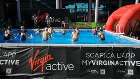 Римини, Италия - июнь 2019: Люди делая аэробику воды на открытом воздухе в бассейне с велосипедом и музыкой видеоматериал