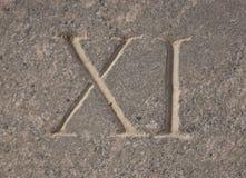Римский цифр - 11 высекаенное в камне стоковое фото rf