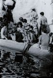 РИМ, ИТАЛИЯ, 1970 - молодой, белокурый женский турист читает книгу тихо пока освежающ ее ноги в фонтане Trevi стоковые фото