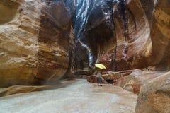 Ринв девушки идя узкий каньон в Petra под желтым зонтиком Стоковые Изображения RF