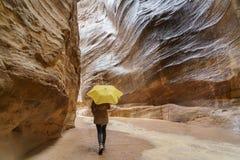 Ринв девушки идя Siq в Petra под желтым зонтиком Стоковые Фотографии RF