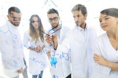 Ринв увиденный общим видом прозрачная доска в химической лаборатории людей анализируя информацию Стоковые Изображения
