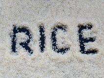 ` Риса ` слова написанное с пальцем на слое белого сырцового риса лежа на темной предпосылке стоковое фото