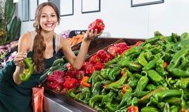 Рисберма продавца женщины нося держа красную и зеленую паприку Стоковое Изображение