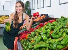 Рисберма продавца женщины нося держа красную и зеленую паприку Стоковое фото RF