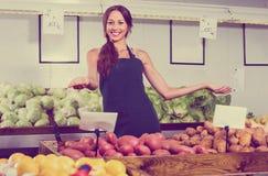 Рисберма продавца женщины нося показывая картошки Стоковое Изображение RF