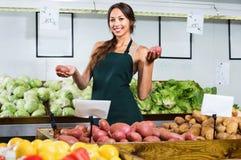 Рисберма продавца женщины нося показывая картошки Стоковое Фото