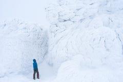 Рискуйте турист в горах около стены снега Стоковое Изображение