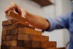 Риск и стратегия планирования в бизнесмене играя в азартные игры устанавливающ woode стоковые фотографии rf