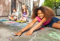 Рисовать на дороге девушка потехи достигая для мела Стоковые Изображения RF