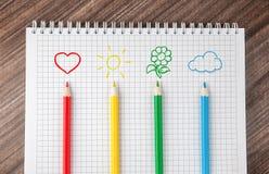Рисовать на тетради с покрашенными карандашами стоковые изображения rf