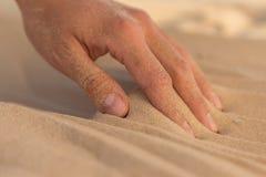 Рисовать руки нашивки в песке Стоковое фото RF