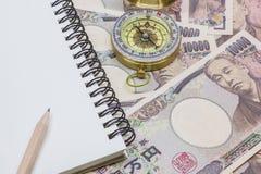 Рисуйте на блокноте, компасе с банкнотами 10 тысяч иены Стоковые Изображения