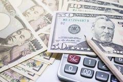 рисуйте, 10 тысяч банкнота иен и банкнота 50 долларов Стоковая Фотография RF