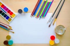 Рисующ поставляет щетки, карандаш, aquarelle, гуашь, бумагу на деревянной предпосылке Стоковые Фото