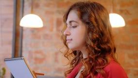 Рисуя хобби сфокусировало женщину делая эскиз к блокноту сток-видео