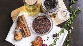 Рис Брайна, черное peper, травы и оливковое масло на прерывая доске f Стоковая Фотография