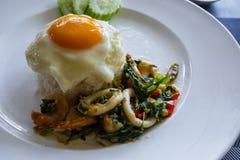 Рис и креветка и кальмар и базилик покрыли с яичницей Стоковая Фотография RF