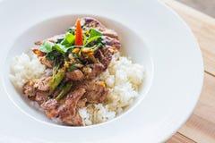 Рис, стейк, стейк свинины с базиликом в белом блюде на деревянной таблице Стоковое Фото