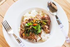 Рис, стейк, стейк свинины с базиликом в белом блюде на деревянной таблице Стоковое Изображение
