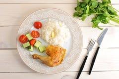 Рис с зажаренной в духовке ногой цыпленк цыпленка и огурец с томатами дальше plat стоковая фотография rf