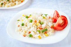 Рис с зажаренными овощами служил с свежим томатом Стоковые Изображения