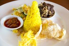 Рис Nasi Kuning индонезийский желтый служил с braised говядиной, shredded яичком, овощами, салатом кокоса, домодельным sambal и ш Стоковая Фотография