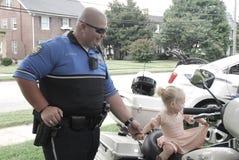 Ричмонд, Ky США - 9-ое сентября 2017 - офицер мотоцикла фестиваля a ребенк держит руку малой девушки стоковые изображения