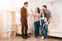 Риэлтор в костюме показывает дом семьи они купила покупая дом принципиальной схемы покупая имущество реальное Стоковая Фотография RF