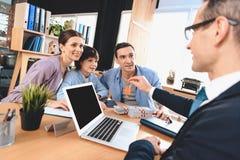 Риэлтор сидя на столе в офисе Риэлтор ключи для новой квартиры к семье стоковое фото rf
