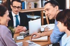Риэлтор сидя на столе в офисе Отец, мать и сын обсуждают план квартиры Стоковое Изображение RF