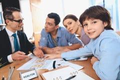 Риэлтор сидя на столе в офисе Отец, мать и сын обсуждают план новой квартиры Стоковая Фотография