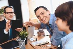 Риэлтор сидя на столе в офисе Отец указывает на таблетку в руках риэлтора Стоковая Фотография RF