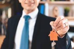 Риэлтор сидя на столе в офисе Риэлтор показывает ключи с значком выреза нового дома стоковое изображение