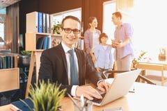 Риэлтор сидя на столе в офисе Риэлтор работает на компьтер-книжке с семьей в предпосылке Стоковое Изображение RF