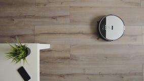 Робототехнический пылесос сползает через современную живущую комнату 4K r акции видеоматериалы