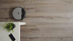 Робототехнический пылесос сползает через современную живущую комнату 4K r видеоматериал
