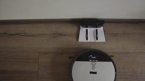 Робототехнический пылесос сползает через современные живущую комнату и тяги в поручать 4K r видеоматериал