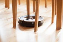 Робототехнический пылесос на чистке слоистого деревянного пола умной технической Стоковое фото RF
